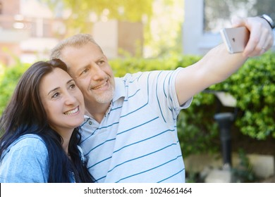 Portrait of middle-aged couple taking selfie with a smartphone