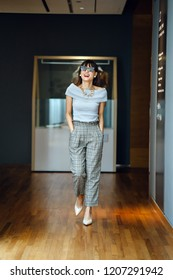 Portrait of a middle-aged,  elegant and attractive Asian Chinese woman. She is walking down a corridor wearing sunglasses and smiling broadly as she exudes confidence and freedom.