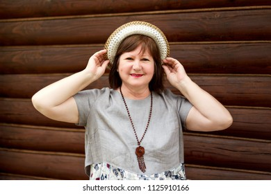 portrait of a middle-aged happy woman bbw in a hat and linen dress near a log wall