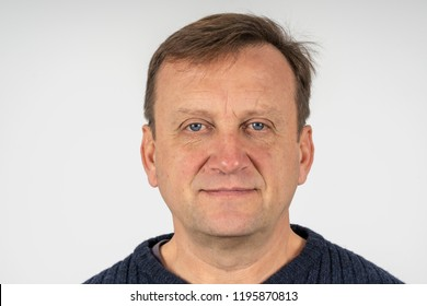 Portrait of a middle-aged man against a white wall background, close up. Photo on document