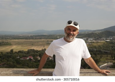 Portrait of a middle-aged man in the background fields and low mountains in white T-shirt and a baseball cap and sunglasses on his forehead