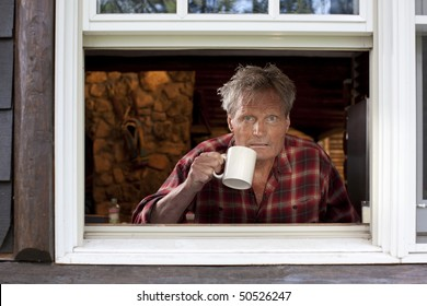 Portrait of a middle-aged man with a plaid shirt, staring out an open window and holding a coffee cup. The image is shot from outside the window, and he is looking at the camera. Horizontal format.