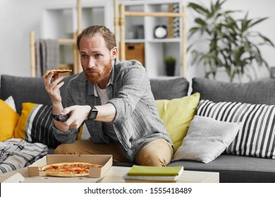 Portrait of middle-aged man watching TV at home and eating pizza during lazy weekend, copy space