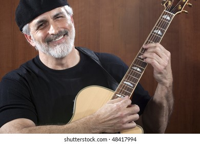 Portrait of a middle-aged man wearing a black beret and t-shirt and playing an acoustic guitar. He is smiling at the camera. Horizontal shot.