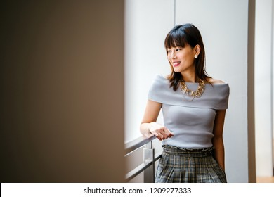 Portrait of a middle-aged, mature Asian Chinese woman in smart casual grey outfit leaning against the railing of a building in the city during the day. She is tall, slim, attractive and smiling.