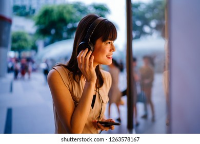 Portrait of a middle-aged, photogenic Chinese woman listening to music on her headphones as she peers into a window display in a mall.