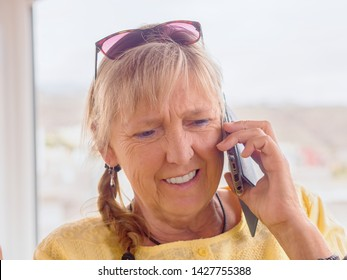 Portrait of a middle-aged woman. She's on the phone with the Movil phone, she's got blond hair, sunglasses on her head, a plaited plait on her side. Background very bright and calm, friendly