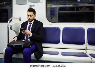 Portrait of Middle-Eastern businessman commuting to work in subway train, using smartphone to listen to music
