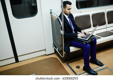 Portrait of  Middle-Eastern businessman in subway train busy working with laptop