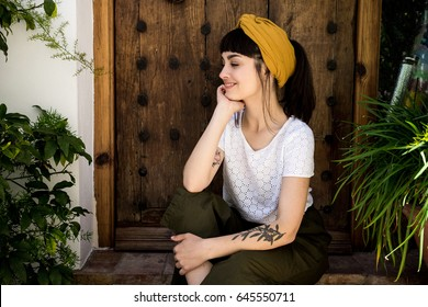 Portrait of millenial traveller with authentic tattoos on her arm and trendy yellow turban decorating her hairstyle resting in old medieval town on coast next to huge wooden door