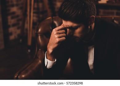 Portrait of minded handsome man in black suit having headache.