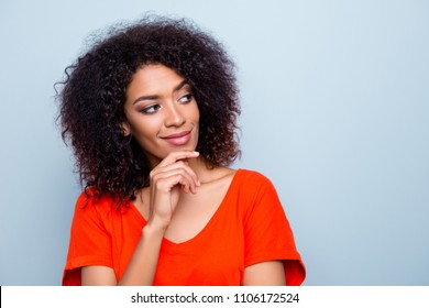Portrait of minded ponder woman in bright outfit holding hand on chin looking at copy-space with smirk isolated on grey background