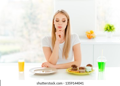 Portrait of minded serious pensive millennial decide choose vegetable have supper lunch confection muffin bakery sit in kitchen table wear trendy beautiful casual style outfit