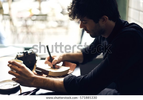Portrait of mindful male author of popular detective stories brainstorming and writing new text noting ideas into personal organizer inspiring by atmosphere in cafe choosing photo for illustration