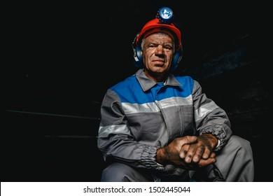 Portrait miner coal man in helmet with lantern in underground mine. Concept industrial engineer.