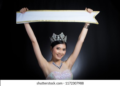 Portrait of Miss Pageant Beauty Contest in sequin Evening Ball Gown long dress sparkle light Diamond Crown, Asian Woman black hair style holding present Empty sash ribbon for country name copy space
