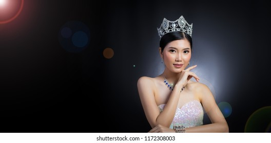 Portrait of Miss Pageant Beauty Contest in sequin Evening Ball Gown long dress with sparkle light Diamond Crown, Asian Woman fashion make up black hair style, studio lighting dark background dramatic