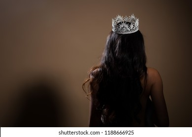 Portrait of Miss Pageant Beauty Contest in open back Evening fur Gown dress with sparkle light Diamond Crown, Asian Woman fashion make up black hair style, turn back side rear view no face