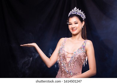 Portrait of Miss Pageant Beauty Contest in Pink sequin Evening Ball Gown with Diamond Crown, Asian Woman points waves hand to side over dark background smoke copy space - Shutterstock ID 1614501247