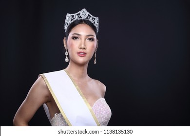 Portrait of Miss Pageant Contest in Asian Evening Ball Gown dress with Diamond Crown empty Sash, fashion make up face eyes love heart hair style, studio lighting black dark background copy space