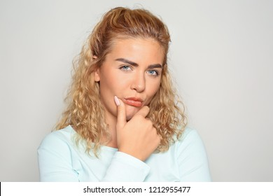 Portrait of mistrustful young woman on light background
