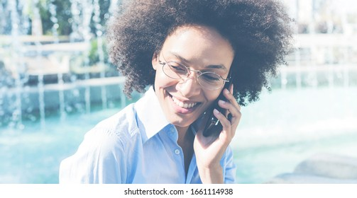 Portrait of mixed race african businesswoman speaking by phone outdoor
