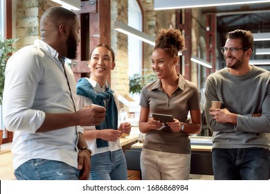 Portrait of mixed race business team having coffeebreak in office. Four colleagues in casual wear are talking while standing in co-working space. Team building concept. Horizontal shot