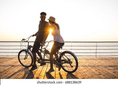 Portrait of a mixed race couple riding on tandem bicycle outdoors near the sea