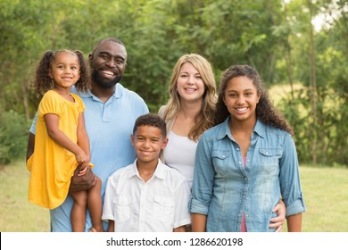 Portrait of a mixed race family laughing.
