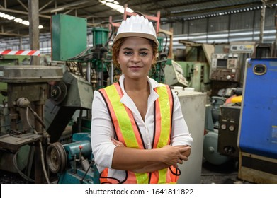 portrait mixed race female engineer working in factory area.