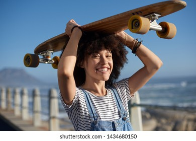 Portrait of a mixed race girl smiling with longboard, happy millennial with skateboard