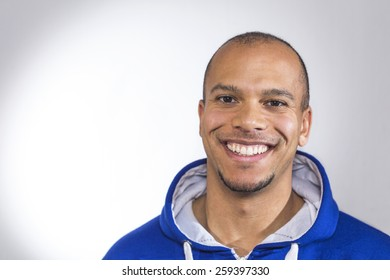 Portrait of a mixed race man smiling to camera in a blue hooded sweater