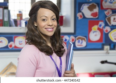 Portrait of a mixed race school teacher. She is holding some school books.