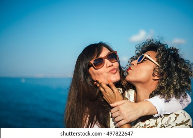 Portrait of mixed race woman with curly hair kisses brunette girl in sunglasses and touching her chin.