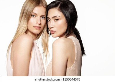 Portrait of mixed races young woman with different types of skin. Friendship of different nationalities concept. Two girls standing and looking at c