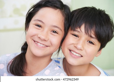 Portrait of mixed-race twins smiling and looking at camera