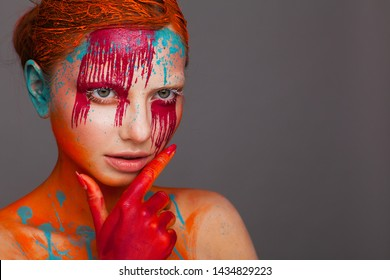 Portrait of a model in an expressive creative style using an unusual make-up. Studio beauty shooting