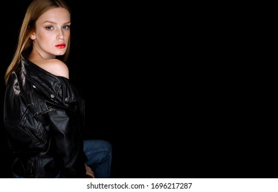 Portrait of a model girl in a black biker leather jacket. young woman with brown hair posing on black background