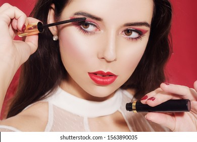 Portrait, model holds mascara in hands and paints eyelashes. Beautiful brunette with professional red make-up, on a red background. New Year's red make-up