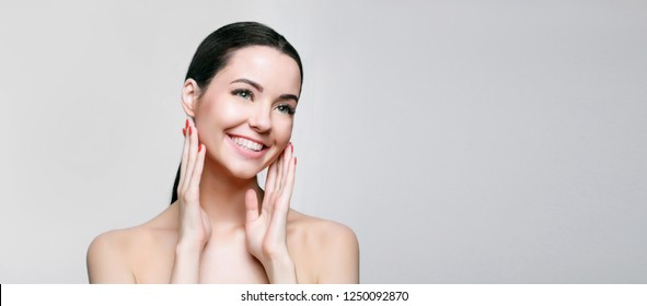 Portrait of model with natural nude make up with bare shoulders on gray background. Beautiful young woman with clean perfect skin. Detox collagen vitamins minerals treatment therapy concept.