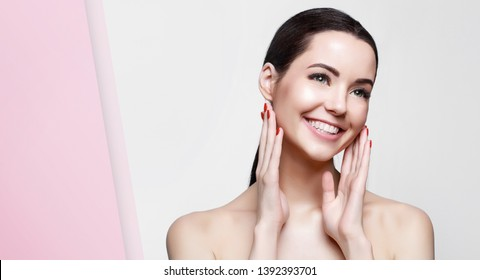 Portrait of model with natural nude make up with bare shoulders on gray background into hole in pink paper. Beautiful young woman with perfect glow clean skin touching her face.