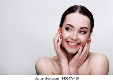 Portrait of model with natural nude make up with bare shoulders on gray background. Beautiful smiling young woman with perfect glow clean skin. Skincare, cosmetology, beauty, fashion concept.