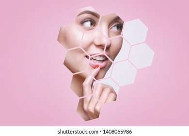 Portrait of model with natural nude make up touching her face in pink hexagon frames. Beautiful happy young woman applying moisturizer cream on her perfect glow clean skin.