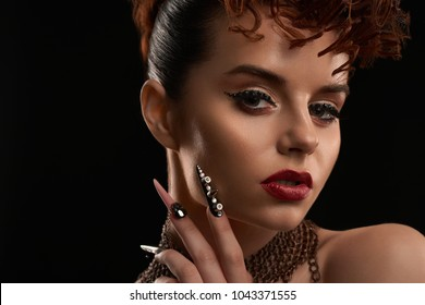 Portrait of model wearing nailart, made in different colors and rhinestones, bright makeup with red lipstick and liner. Girl has fashionable hairstyle. Woman is wearing thin chains on her neck.