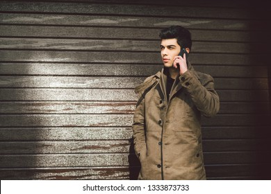 Portrait of a model young male Turkish Mediterranean race brunet in coat uses hand phone technology businessman on the street in sunny weather against the background of a wooden wall.