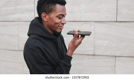 Portrait modern african man holding in hands smartphone using voice command recorder, assistant or takes calling, looking at phone on city street on gray wall background