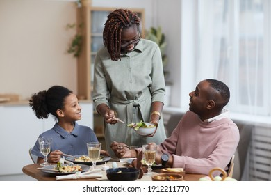 Portrait of modern African-American woman serving food for family while enjoying dinner together in cozy home interior, copy space - Shutterstock ID 1912211770