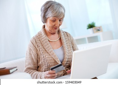 Portrait of modern aged female shopping through internet