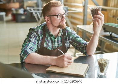 Portrait of modern bearded  barista holding glass of coffee beans while checking quality of roast in artisan roastery, copy space