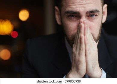 Portrait of modern bearded businessman looking at camera with red teary eyes, stressed and tired against black background, closing his mouth with hands